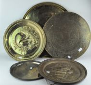 A group of five trays, most brass,