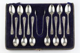 An early 20th century cased set of twelve silver teaspoons with matching sugar tongs,