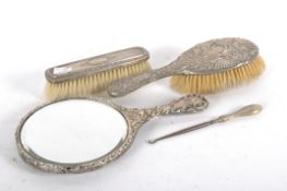 A silver and white metal backed brush set,