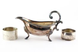 A mid century silver sauce boat raised upon three hoof feet, with ribbed border,