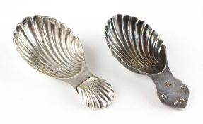 A silver shell-shaped caddy spoon and a white similar white metal example,
