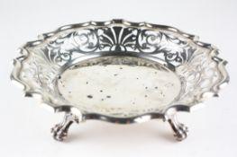 An Edwardian silver dish with pierced rim, raised upon three lion paw feet,