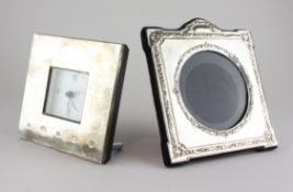 A modern silver photo frame of square form with embossed floral decoration,