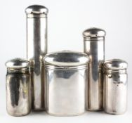 An Edwardian five piece silver set of travelling toiletries containers by Asprey & Co,