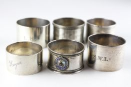 A assortment of six silver napkin rings of varying shapes and designs,