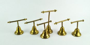 A group of six brass Glover & Barnes (London) brass T-bar weights, in sizes, on bell-shaped bases,