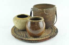 An antique tribal basket with leather handle and two basket weave plates;