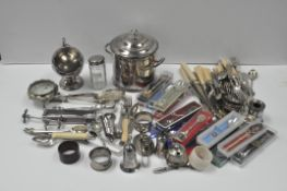 A collection of silver plated wares, including: casters, a biscuit barrel and cover, tongs, cutlery,
