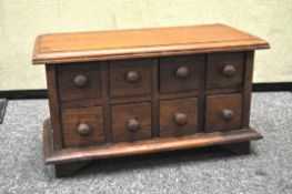 A wooden eight drawer table top spice cabinet,