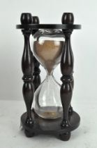 A vintage glass timer, with turned supports and wooden mount,