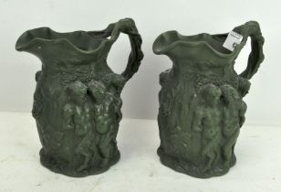 A pair of relief-moulded stoneware jugs,