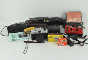 A collection of compact cameras, including a Canon sure shot AF-7,