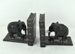 A pair of carved Sri Lankan ebony and bone inlaid book ends, in the form of elephants,
