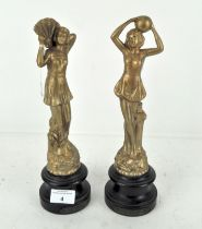 A pair of early 20th century figures of ladies, raised on turned wooden bases,