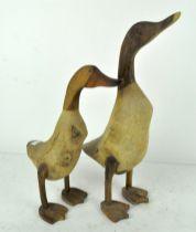 Two wooden sculptures of ducks,