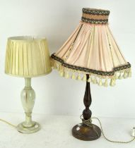 A turned mahogany table lamp together with a polished stone example, both with shades,