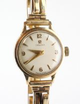 A yellow gold omega wristwatch. Circular champagne dial with mixed markings.
