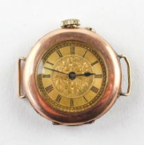 A rose and yellow metal cased watch. Circular gold dial with roman numerals and engraved design.