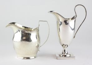 A silver cream jug, of slightly swollen form with chased decoration and a crest beneath the spout,