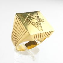A large yellow metal square head signet ring with masonic engraving.