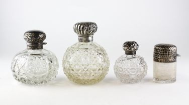 Three Edwardian silver topped cut-glass scent bottles and stoppers, each of globular form,