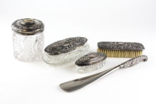Five silver-mounted dressing table items, with embossed designs, including lidded powder bottles,