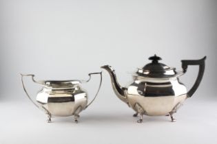 A George V silver teapot of octagonal form, raised upon four feet,