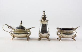 A three piece silver cruet set, comprising lidded mustard, open salt and a pepper pot,
