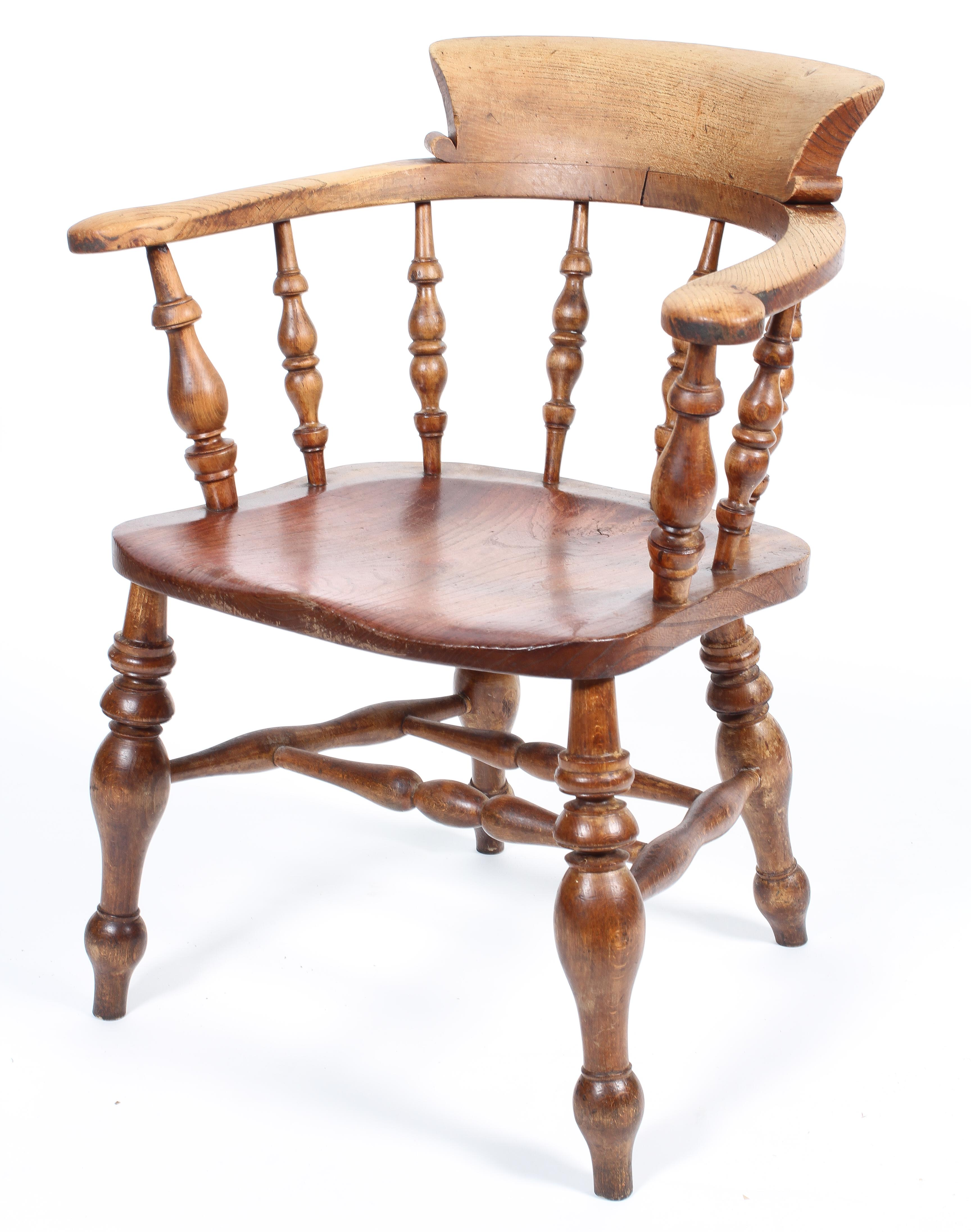 An elm smoker's bow chair, with turned spindles and solid seat,