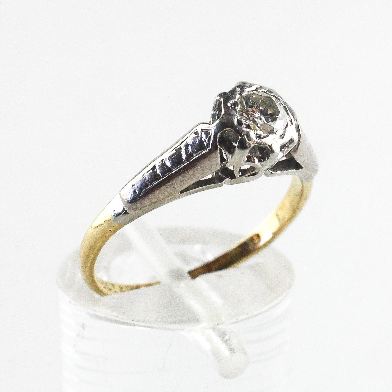 A yellow and white metal ring. Illusion set with a round brilliant cut diamond