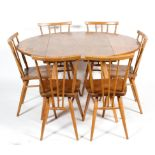 An Ercol elm and beech circular folding dining-table and six spindle back dining chairs,