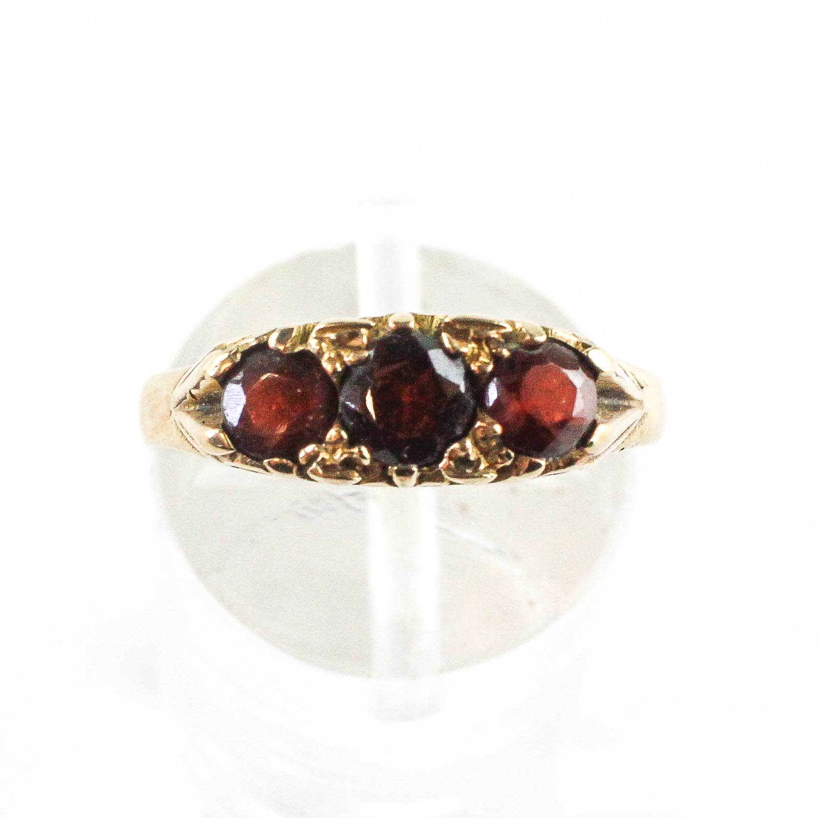 A yellow metal carved half hoop ring set with three round cut garnets. - Image 2 of 3