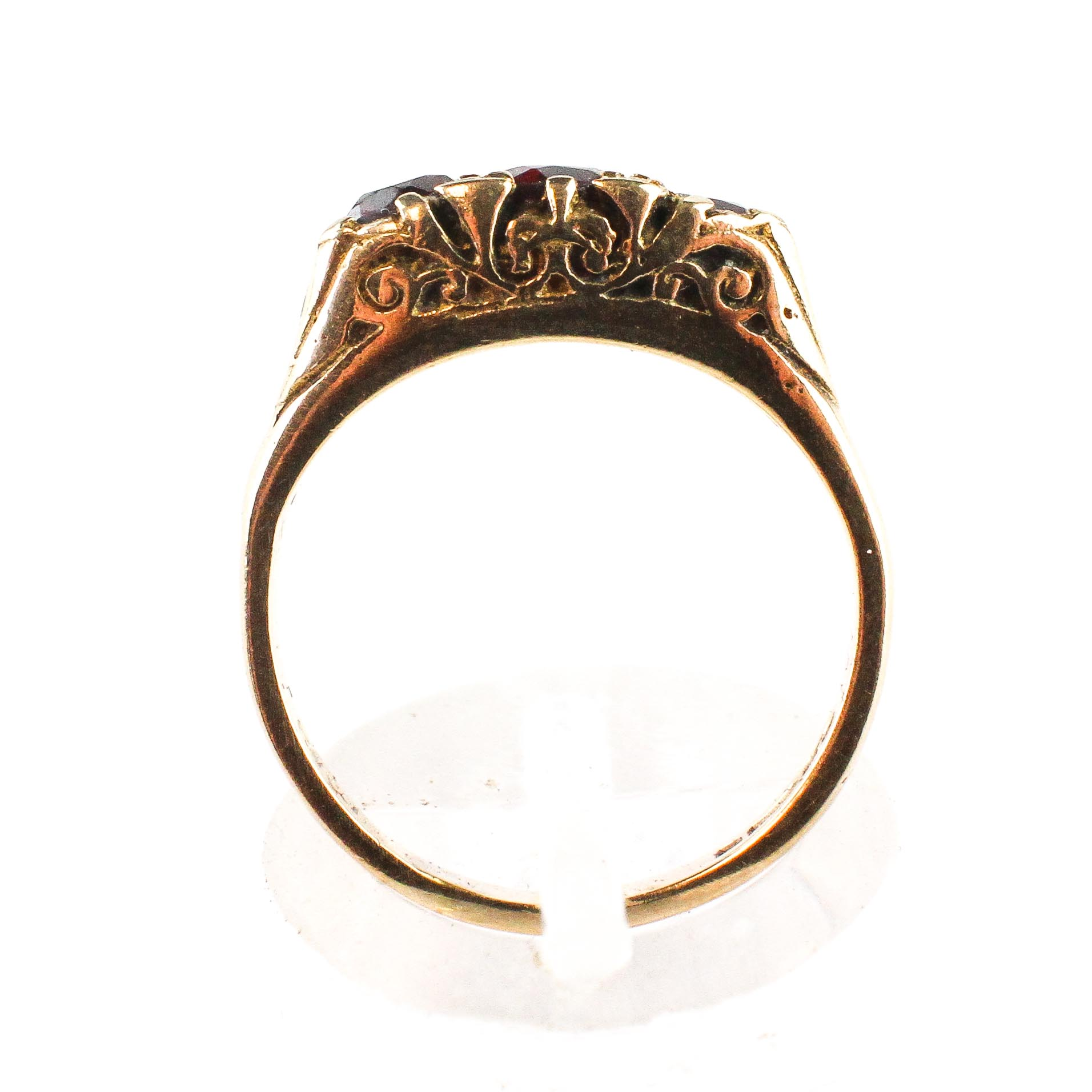 A yellow metal carved half hoop ring set with three round cut garnets. - Image 3 of 3
