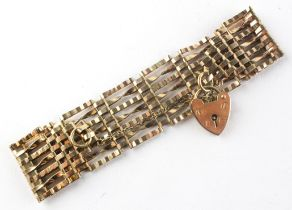 A yellow metal 23.0mm wide seven bar gate bracelet with padlock and fitted safety chain.