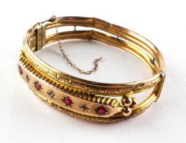 A yellow metal bangle set with synthetic rubies and rose cut diamonds.