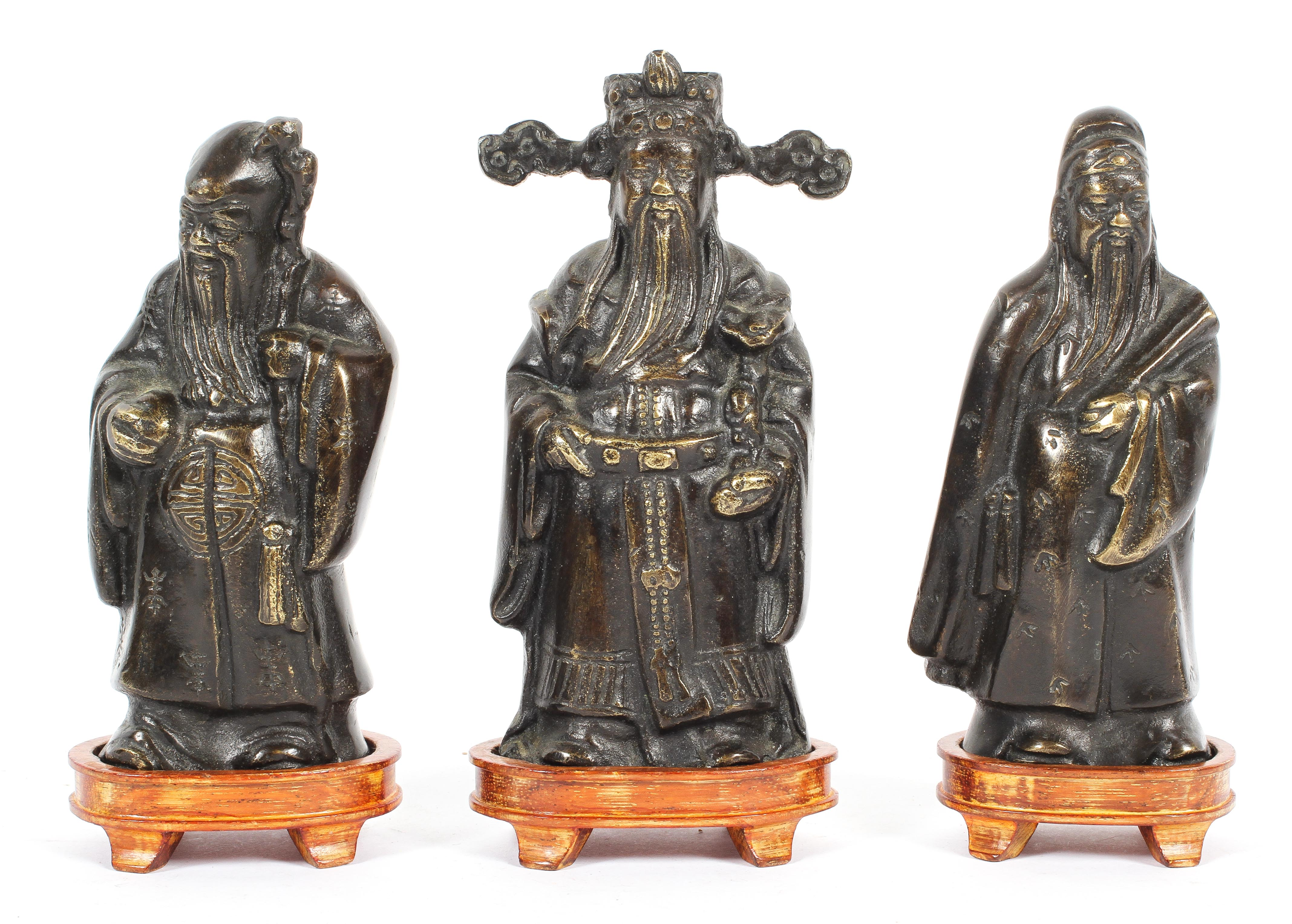 Three Chinese bronze figures of Immortals, on wooden stands, 20th century,