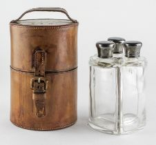 An Edward VII Campaign style leather cased travelling set of three silver mounted glass bottles,