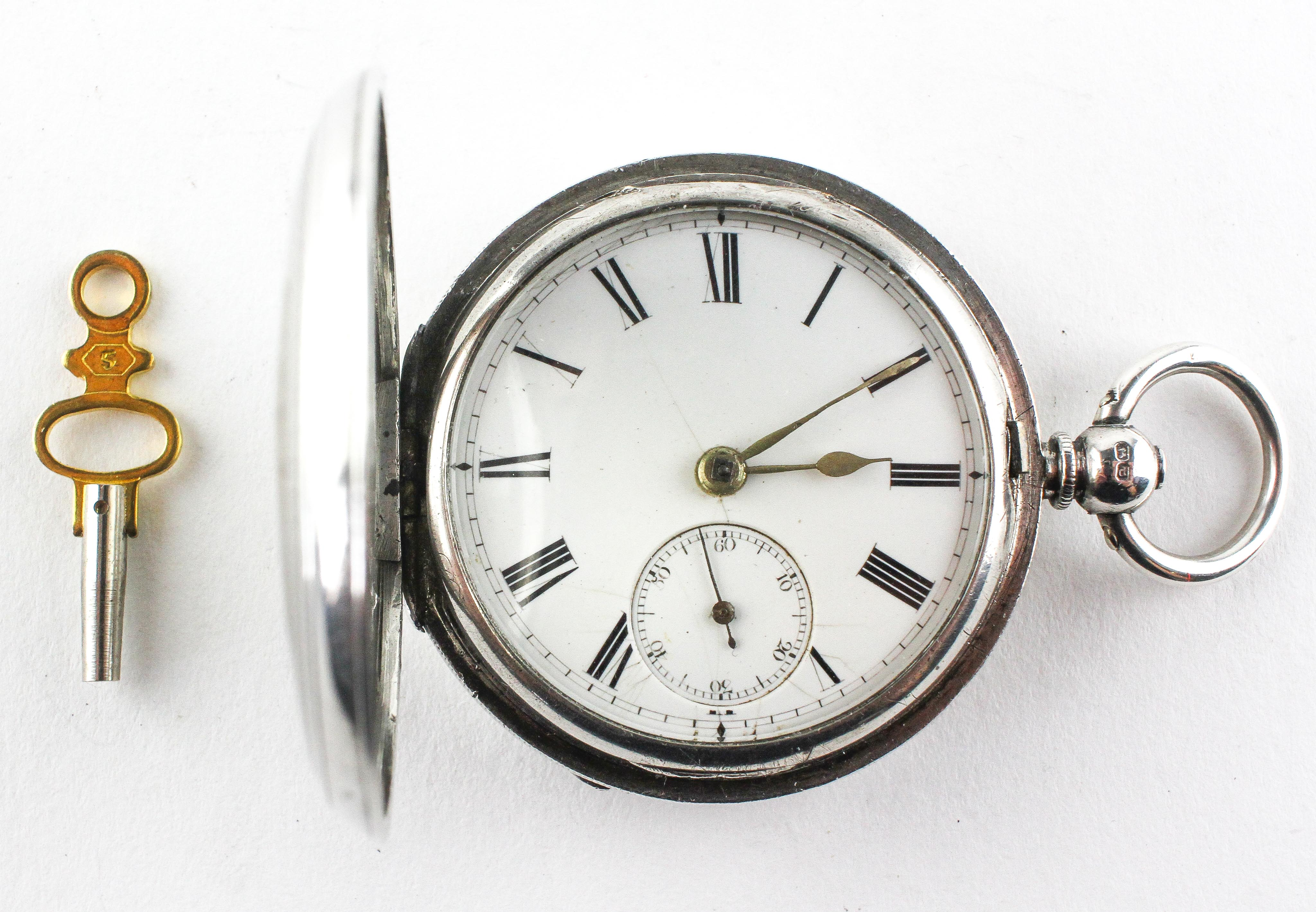 A full hunter pocket watch. Circular white dial with roman numerals. Key wound movement.