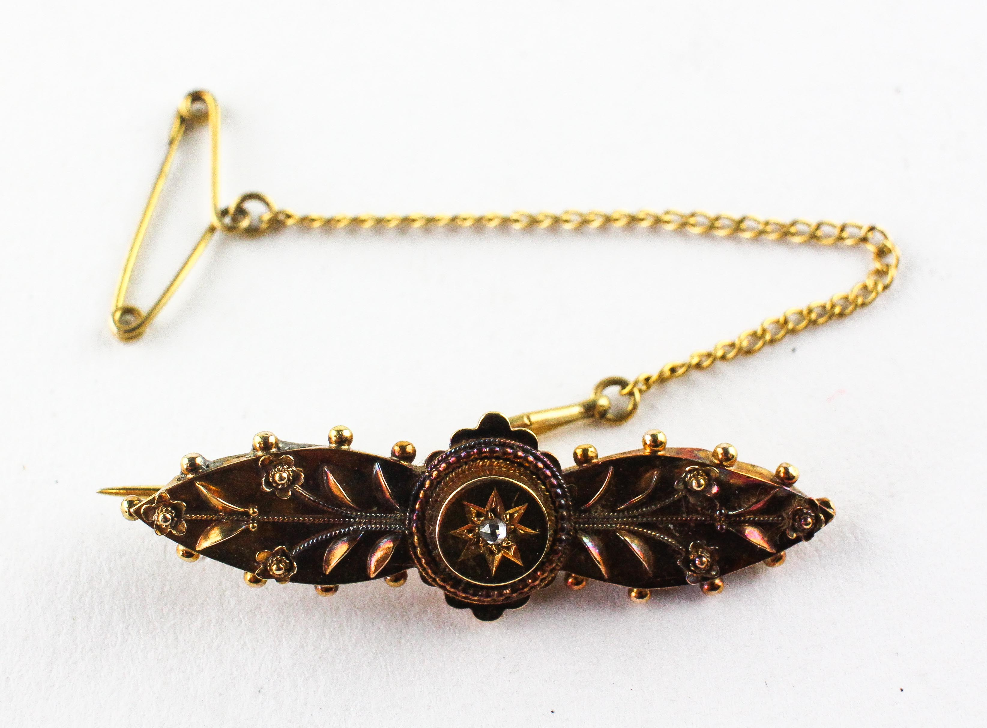 A yellow metal ornate bar brooch set with a rose cut diamond to centre. Stamped 15ct