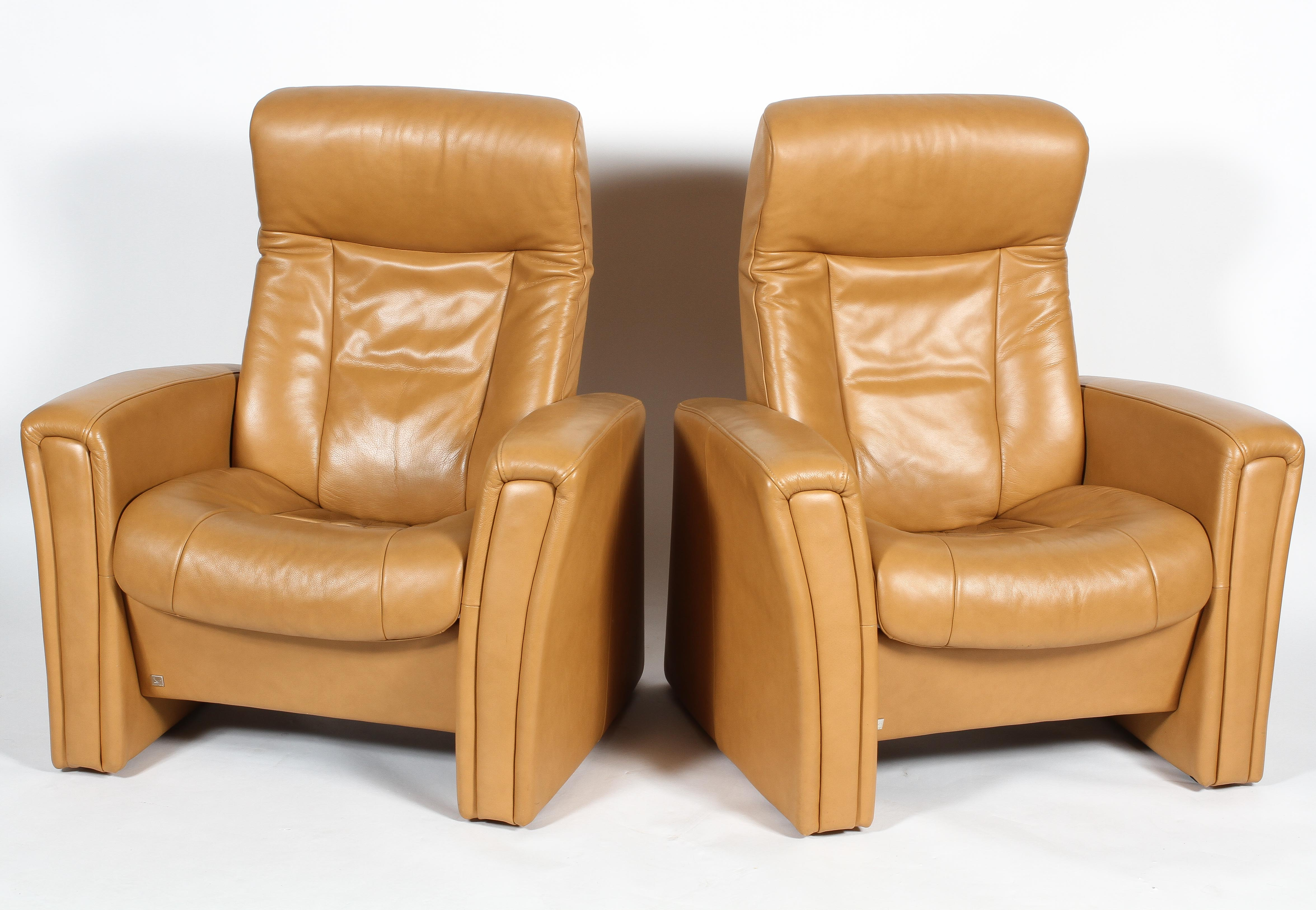 Two Fjords (Norwegian) reclining chairs, upholstered in pale tan leather style fabric,