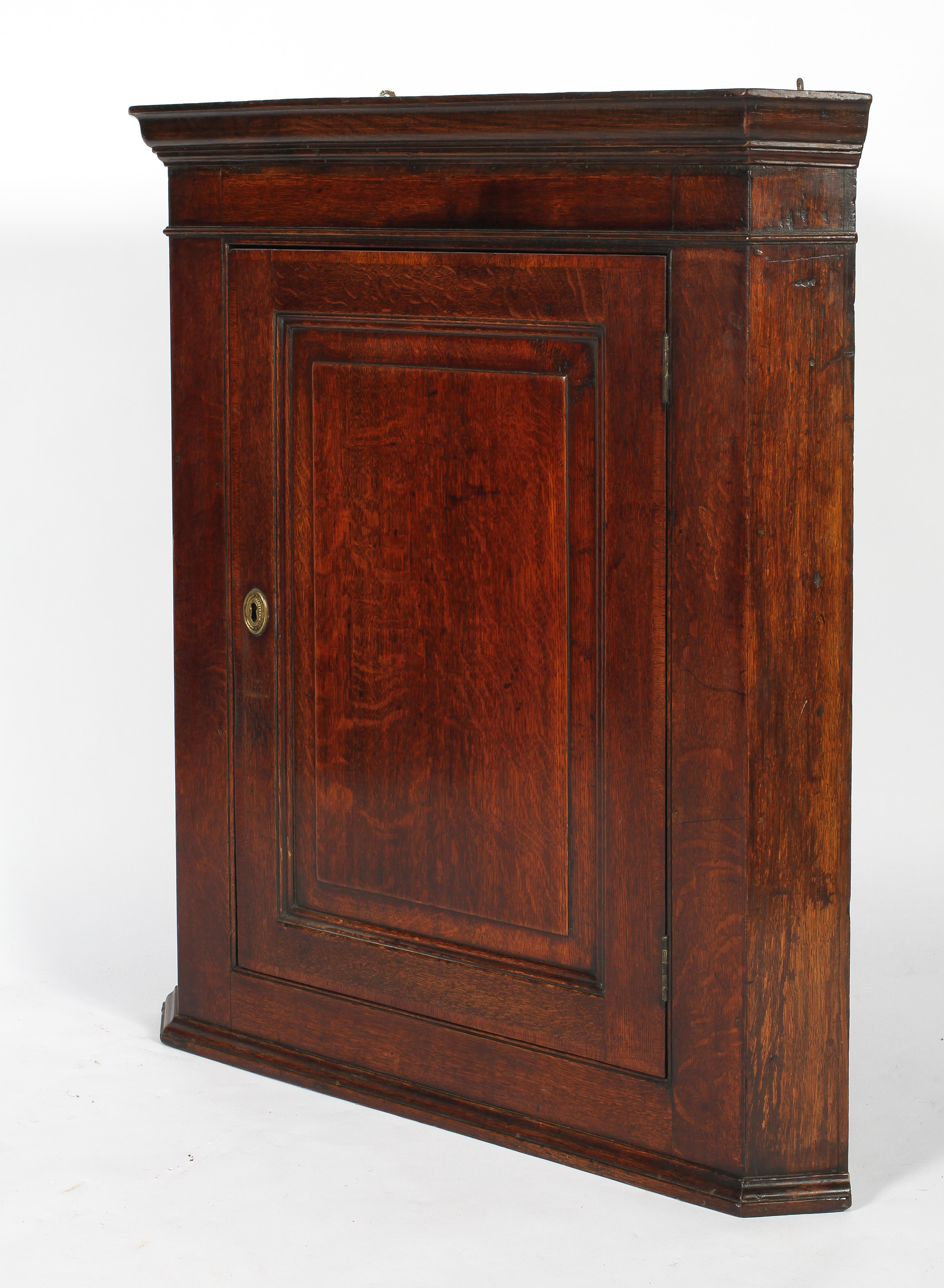 An 18th century oak corner cupboard, with moulded cornice and panelled door,