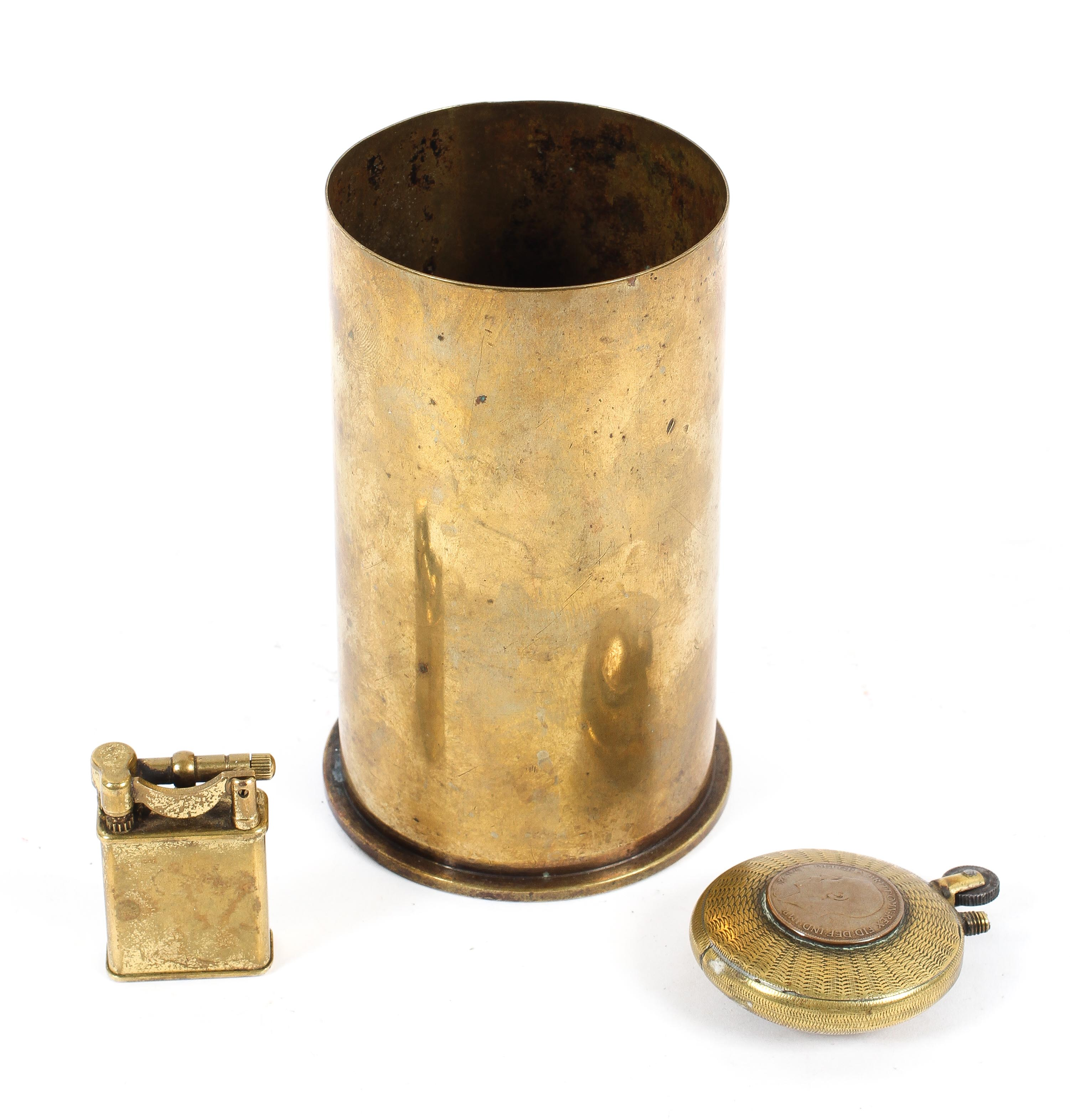 Two trench art lighters together with a brass shell case,