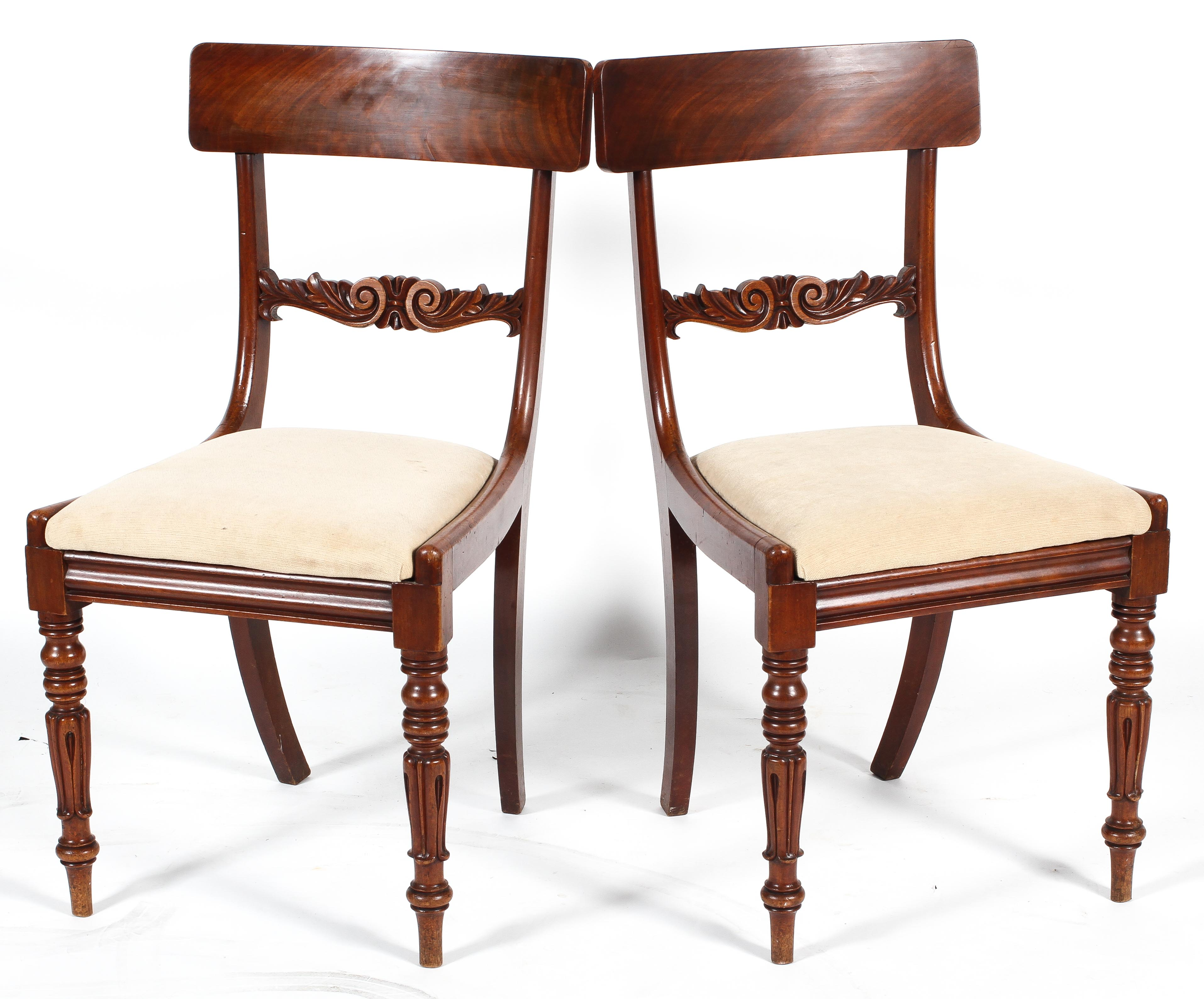 A pair of Regency style mahogany dining chairs with bar backs, drop in seats and turned front legs,