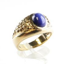 A yellow metal ring set with an oval cabochon synthetic star sapphire. No hallmark - stamped 10K.