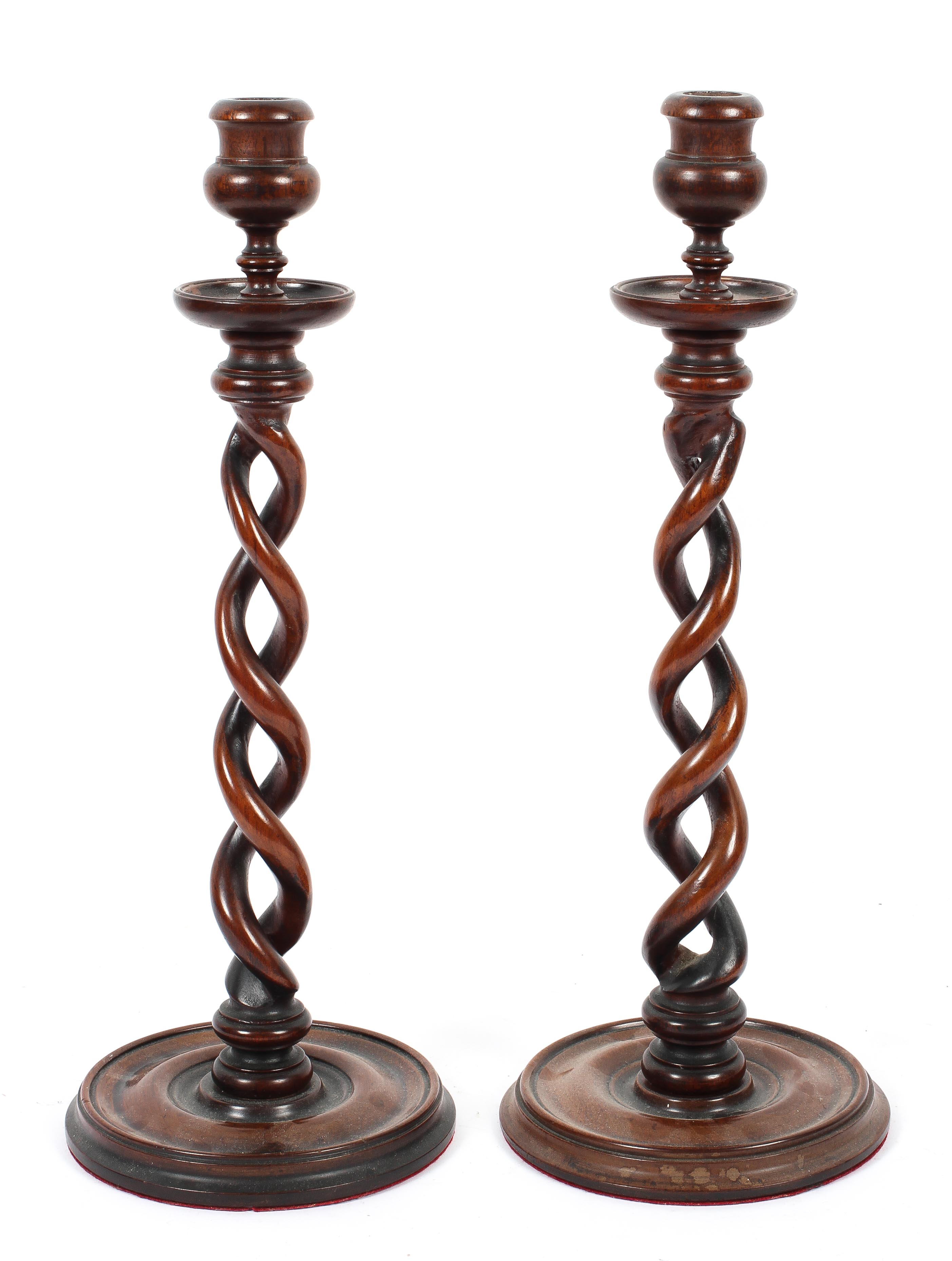 A pair of barley twist mahogany candlesticks, with baluster turned sconces,