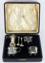A George V cased silver four piece cruet set, of hexagonal form with blue glass liners,