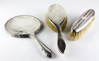 A silver backed dressing table mirror (lacking glass), a handled brush and a clothes brush,