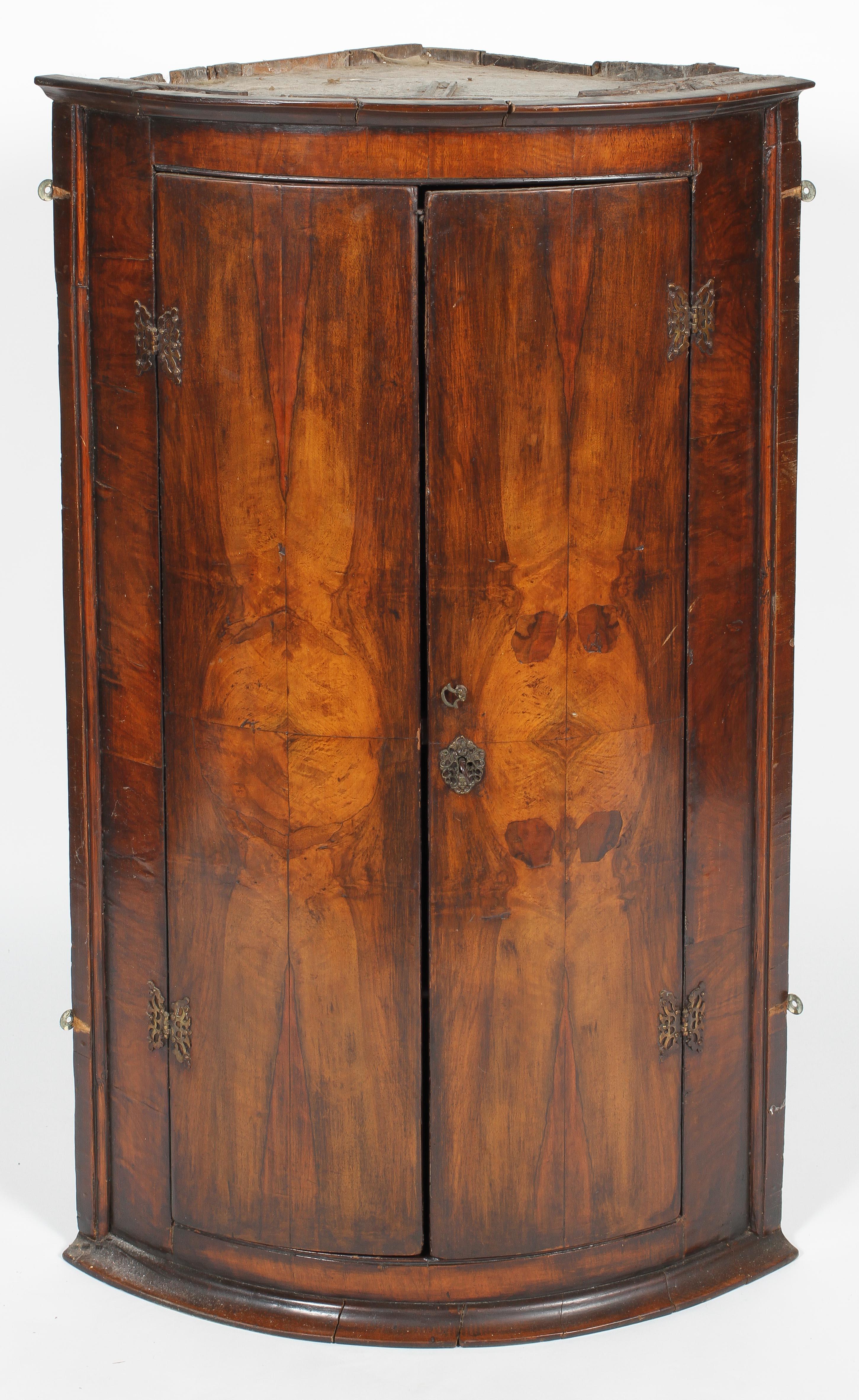 A 19th century walnut corner cupboard, of D-shape section, revealing three shelves,