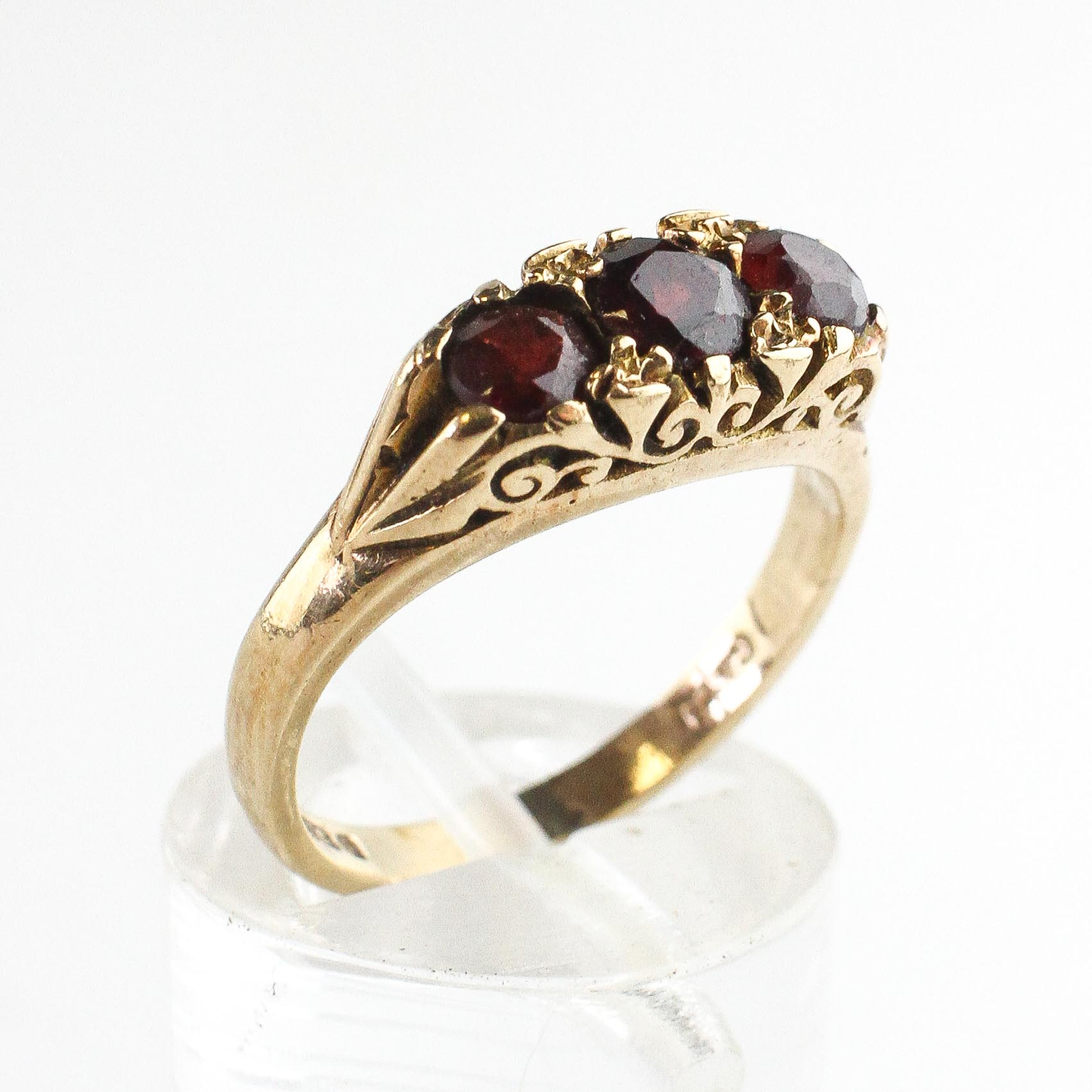 A yellow metal carved half hoop ring set with three round cut garnets.