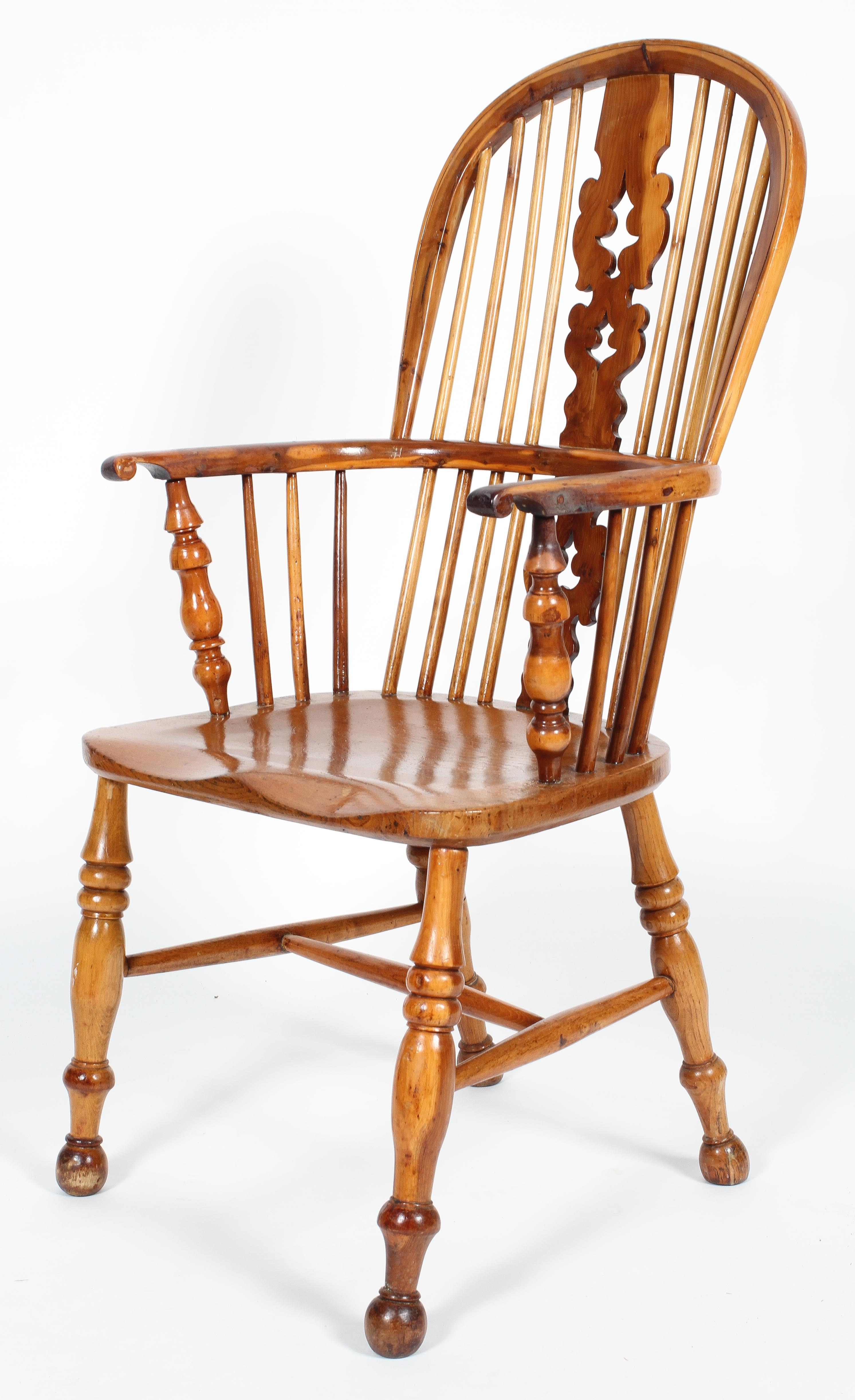 An oak and yew Windsor chair, with pierced scroll splat and baluster arm supports,